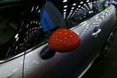 Красное зеркало автомобиля левой стороны с отражением современного автомобиля Детали экстерьера автомобиля Стоковое Фото
