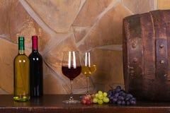 Красное и белое вино около старой бочки в винном погребе Стоковые Изображения RF
