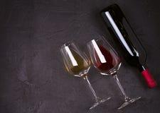 Красное и белое вино с плитой сыра Бокалы с сыром, виноградинами, смоквами и гайками на черной предпосылке Стоковая Фотография