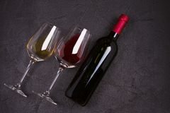 Красное и белое вино с плитой сыра Бокалы с сыром, виноградинами, смоквами и гайками на черной предпосылке Стоковое Фото