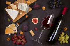 Красное и белое вино с плитой сыра Бокалы с сыром, виноградинами, смоквами и гайками на черной предпосылке Стоковые Фото