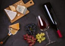 Красное и белое вино с плитой сыра Бокалы с сыром, виноградинами, смоквами и гайками на черной предпосылке Стоковое фото RF