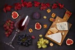 Красное и белое вино с плитой сыра Бокалы с сыром, виноградинами, смоквами и гайками на черной предпосылке Стоковые Изображения RF