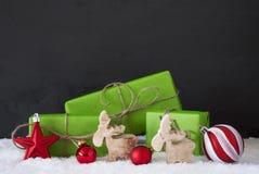 Красное и зеленое украшение рождества, снег, черная стена цемента Стоковое Изображение RF