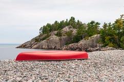 Красное каное на скалистом пляже Стоковая Фотография RF