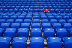 Красное кресло в ряд голубых кресел различные дискеты белые Specia стоковые изображения