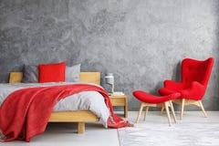 Красное кресло в спальне стоковая фотография