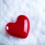 Красное лоснистое сердце на морозной белой предпосылке снега Влюбленность и концепция валентинки St Стоковое фото RF