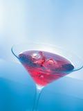 Красное питье коктеиля с кубами льда на голубых светлых предпосылке подкраской, потехе и диско танца Стоковые Фотографии RF