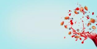 Красное питье сока или smoothie полито из стеклянной бутылки с ингридиентами выплеска и ягод на предпосылке, знамени или t бирюзы Стоковая Фотография RF