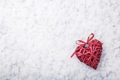 Красное плетеное сердце на снеге стоковые изображения rf