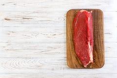 Красное свежее сырцовое филе телятины говядины на разделочной доске Белая деревянная предпосылка с космосом экземпляра стоковые изображения