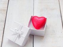 Красное сердце внутри белой подарочной коробки над белой деревянной предпосылкой Стоковое Изображение