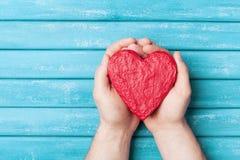 Красное сердце в взгляд сверху рук Концепция здоровых, влюбленности, органа пожертвования, дарителя, надежды и кардиологии имеющи