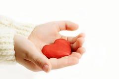 Красное сердце в руках Стоковое Изображение