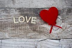 Красное сердце на деревянной предпосылке с влюбленностью слова Стоковые Фотографии RF