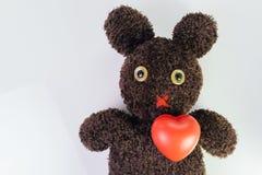 Красное сердце на милой коричневой handmade пушистой кукле с pitty глазами, здравоохранение для детей или дети, медицинский уча к стоковое изображение