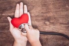Красное сердце на руке ` s женщины и девушке маленького ребенка рассматривает Стоковая Фотография