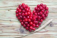 Красное сердце вишни на деревянной таблице Стоковые Изображения RF