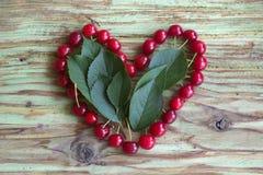 Красное сердце вишни на деревянной таблице Стоковое фото RF