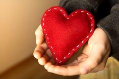 Красное сердце в руках Стоковые Изображения