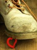 Красное сердце задавленное тяжелым, старым воинским ботинком Стоковые Изображения