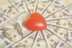 Красное сердце и 100 банкнот доллара Стоковые Изображения