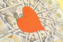 Красное сердце и 100 долларовых банкнот для предпосылки Стоковые Изображения