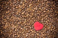 Красное сердце на предпосылке кофейных зерен стоковая фотография