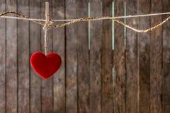 Красное сердце с смертной казнью через повешение зажимки для белья на веревке для белья Стоковая Фотография