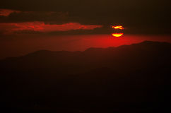Красное солнце установленное над холмами z Стоковая Фотография RF