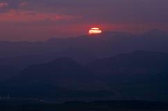 Красное солнце установленное над холмами z Стоковые Фото