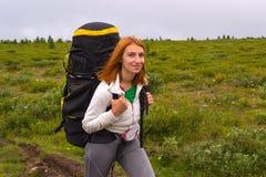 Красное с волосами милое перемещение девушки с большими черными рюкзаком и бутылкой стоковая фотография rf