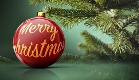 Красное украшение шарика рождества перед реальным деревом стоковое фото