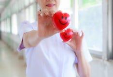 Красное усмехаясь сердце держало путем усмехаясь женские руки ` s медсестры в больнице или клинике здравоохранения Профессионал,  стоковая фотография rf