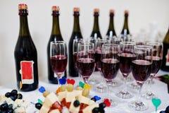 Красное шампанское на бутылках предпосылки стекел на приеме Стоковая Фотография