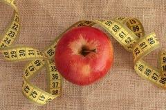 Красное яблоко и желтая измеряя лента Стоковая Фотография
