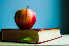 Красное яблоко и красный трудный конец книги крышки вверх на голубой предпосылке Яблоко знания - метафоры стоковые изображения