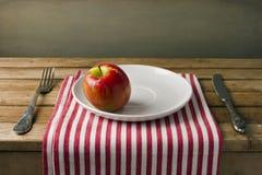 Красное яблоко на белой плите стоковое фото