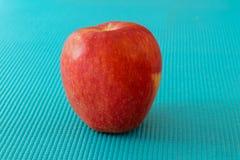 Красное яблоко на небесно-голубой поверхности текстуры стоковая фотография rf