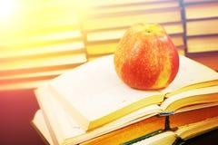 Красное яблоко на раскрытой книге стоковые изображения