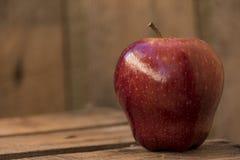 Красное яблоко на старом деревянном столе Стоковое Изображение RF