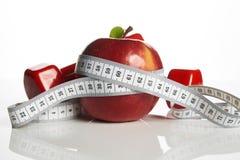 Красное яблоко с измеряя гантелями ленты и веса Стоковая Фотография RF
