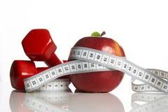 Красное яблоко с измеряя гантелями ленты и веса Стоковые Изображения