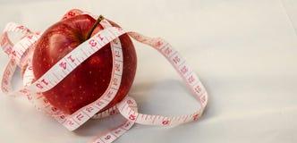 Красное яблоко с лентой measurig, весит концепцию потери Стоковое фото RF