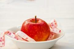 Красное яблоко с лентой measurig, весит концепцию потери Стоковые Фото