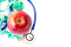 Красное яблоко, измеряя лента и стетоскоп на белой предпосылке Стоковые Изображения RF