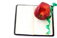 Красное яблоко и измеряя лента на тетради Стоковые Фото