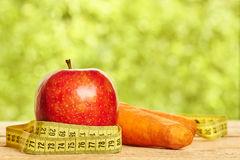 Красное яблоко, и морковь с измеряя лентой Стоковые Фото