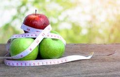 Красное яблоко и яблоко зеленого цвета с измеряя лентой Стоковые Фото
